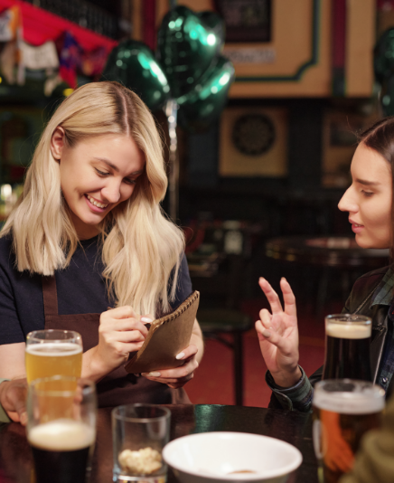 happy young blond waitress workwear writing down orders clients notepad while brunette girl ordering two glasses beer pub